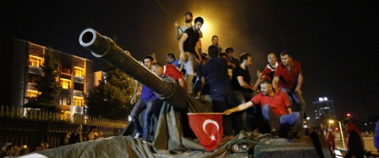 People stand on a Turkish army tank in Ankara