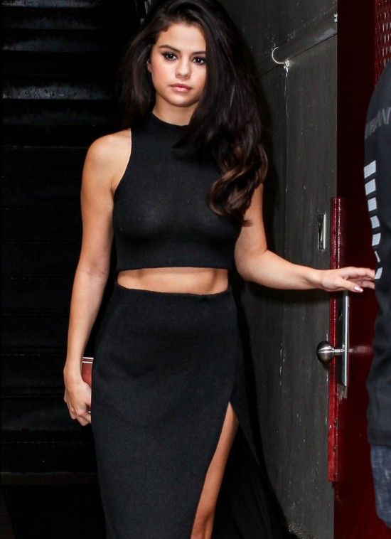 Selena Gomez shows off her toned tummy and legs with a thigh high split skirt and crop top as she goes out in NYC