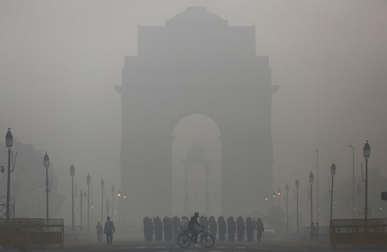 A man rides his bicycle next to Indian soldiers marching in front of India Gate on a smoggy morning in New Delhi