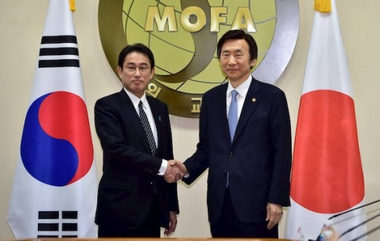 South Korean Foreign Minister Yun Byung-Se shakes hands with his Japanese counterpart Fumio Kishida during their meeting at the Foreign Ministry in Seoul